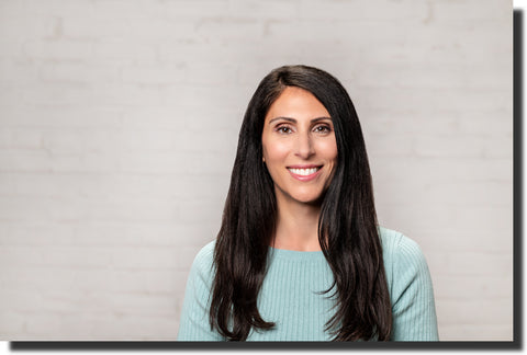 Founder of tTheoderma Skin Care Savy Guthrie.  Woman with long dark brown hair in a sea foam green sweater, smiling.