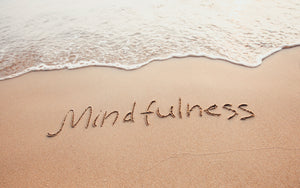 the word mindfulness written in the sand at the water's edge
