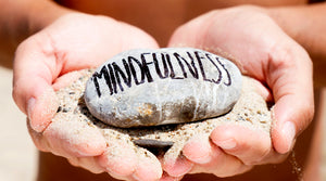 two hands cupped holding flat gray rock and some sand, the word mindfulness written on the rock in black magic marker