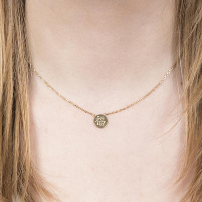 model with blonde hair wearing happiness good fortune gold chinese character necklace in silver