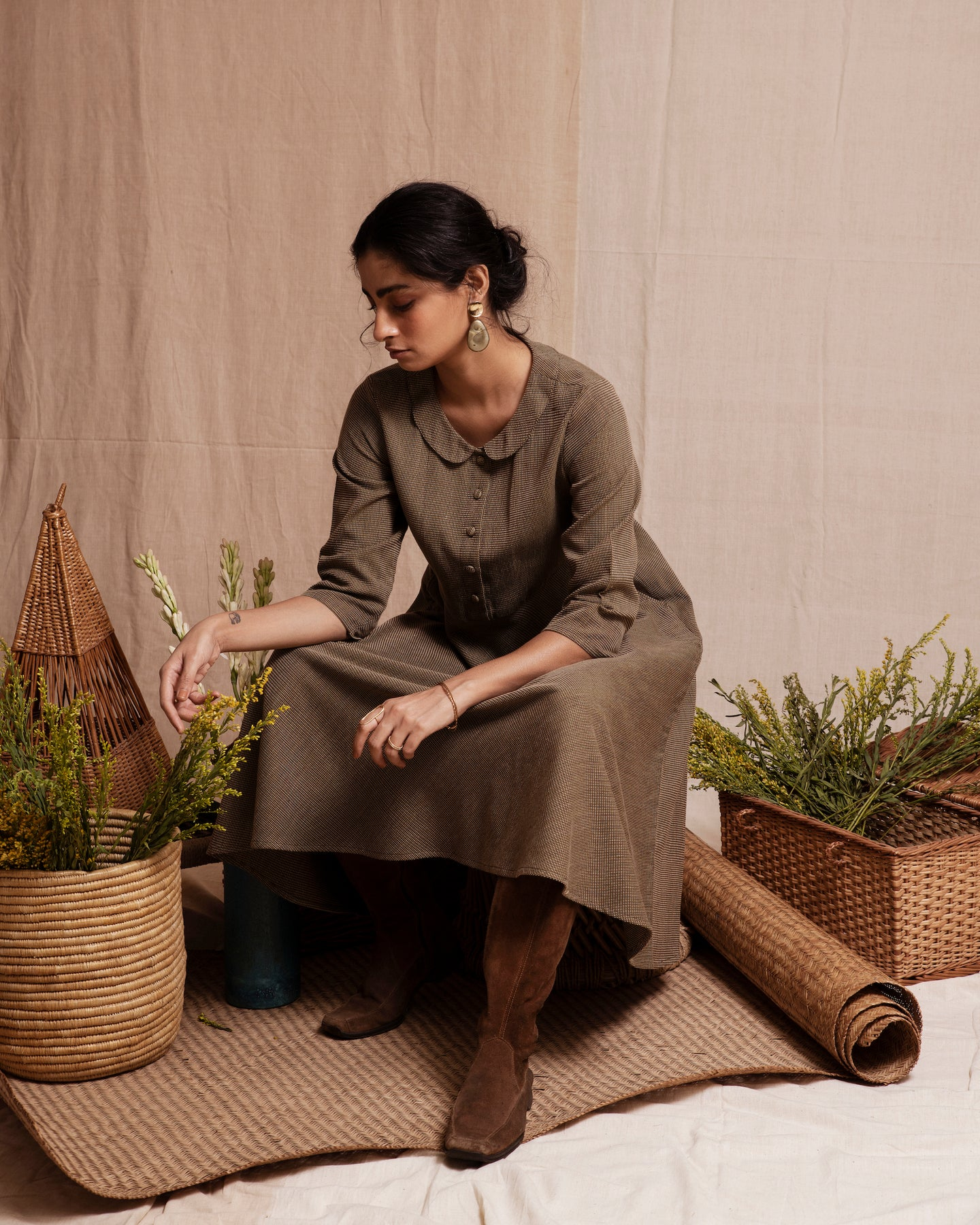 Girl sitting wearing an olive dress with brown boots