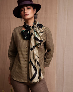 Girl wearing hat, scarf, and olive full sleeves shirt