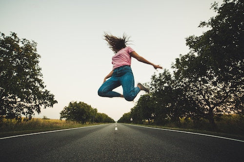 girl jumping in the air on the road