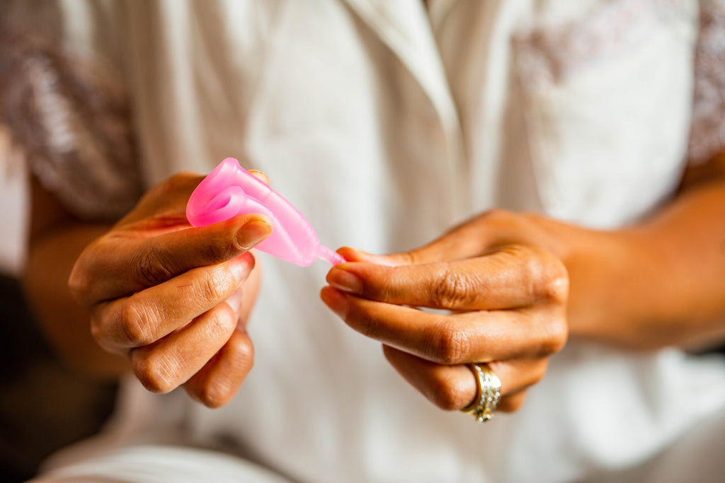 Woman folding BeYou menstrual cup in hand