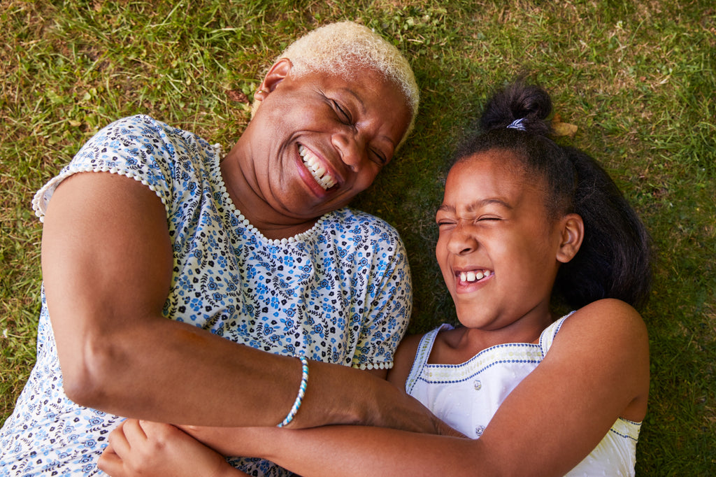 Grandmother and granddaughter laying on grass, laughing together