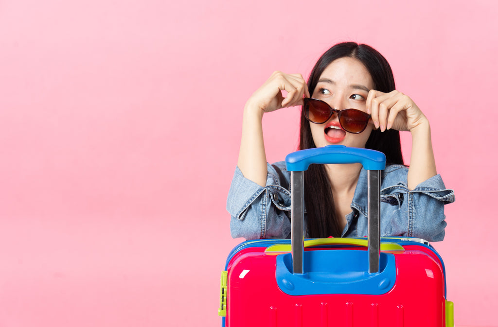 Travelling woman looking over sunglasses leaning against suitcase