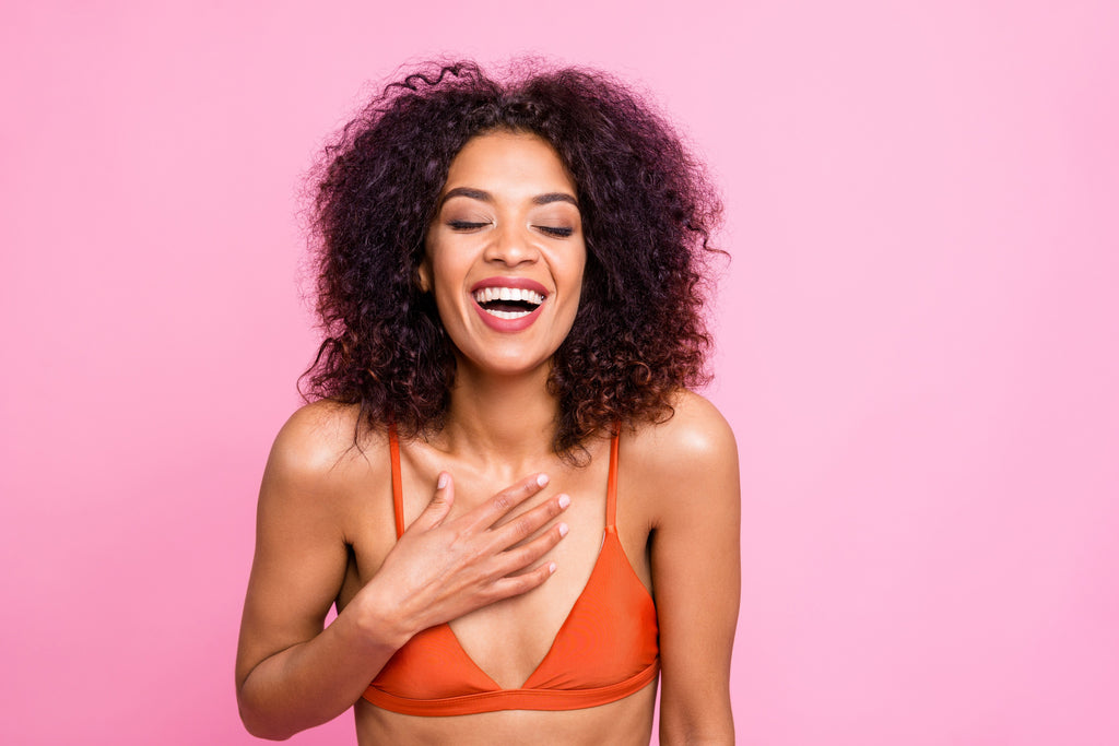 laughing woman wearing an orange bra