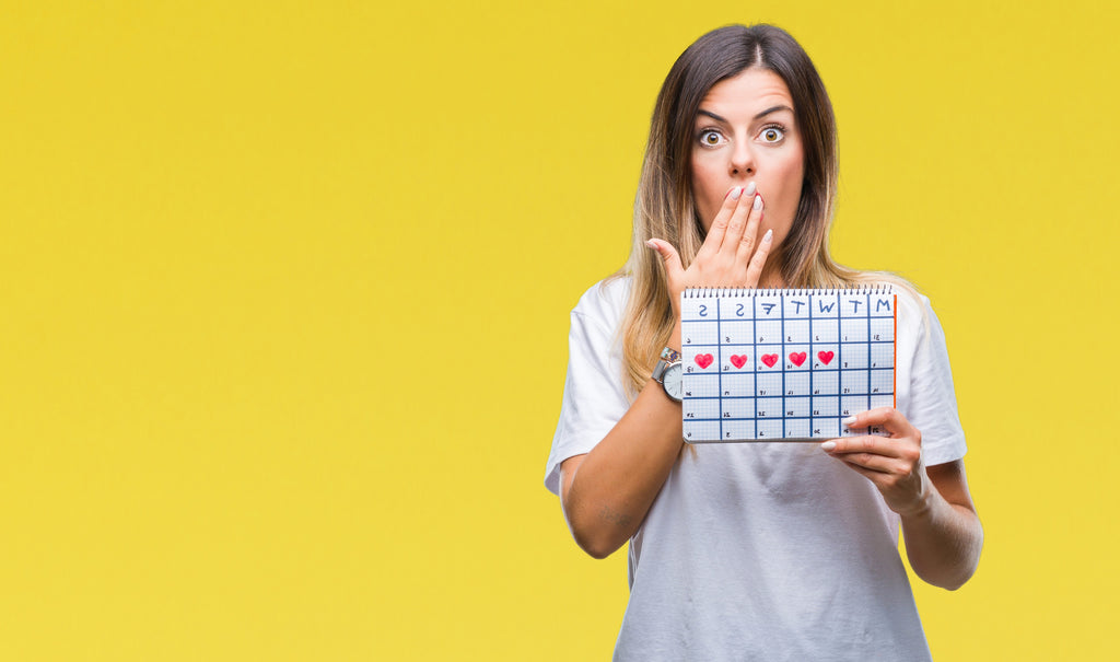 Woman holding up calendar with her period days on it