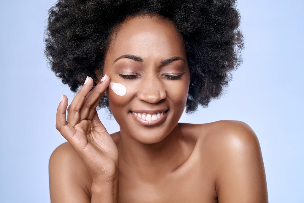 Woman applying skin cream and smiling