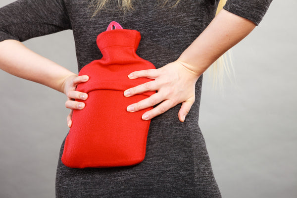 Woman holding hot water bottle on her lower back