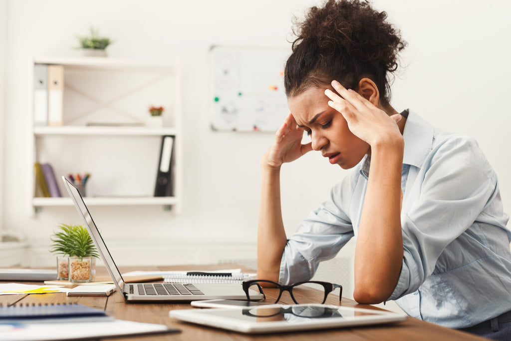 Woman sat at desk looking stressed with head in hands