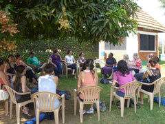 Participants listening to Sister Mary speak on maternal mortality in Uganda