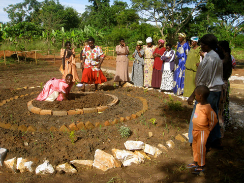 Some of the Women's Group Members plant an organge tree in honour of Harriet
