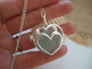 heart locket lovers holding hands with sea glass marble