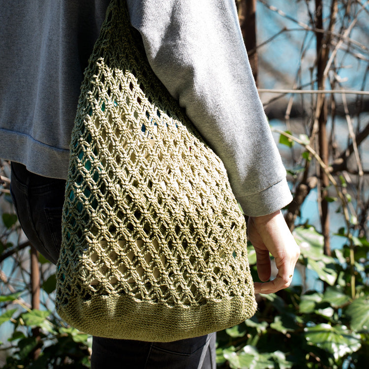 Model carrying Dunya Market Bag made with Urth Yarns Dunya Market Bag Kit and Monokrom Cotton DK yarn in color #1208