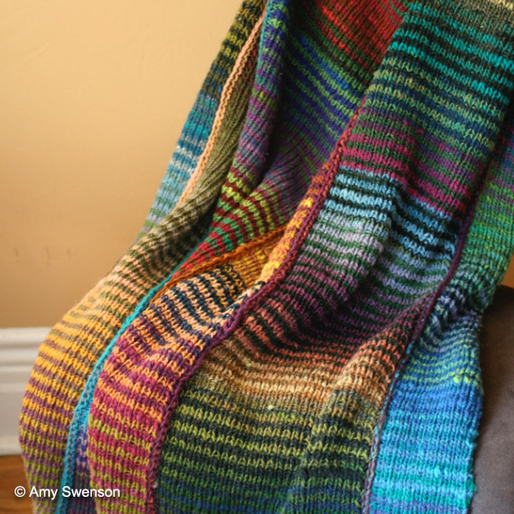 64 Crayons Blanket hung on chair, knit using various colors from Noro's Kureyon