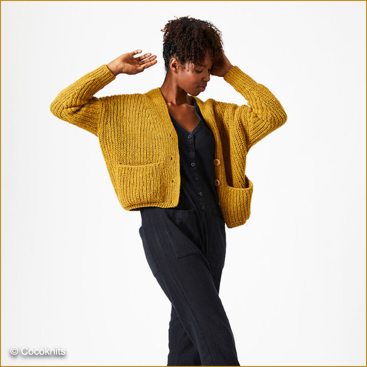 Woman wearing Sarah knit jacket by Cocoknits knit in DK weight yarn