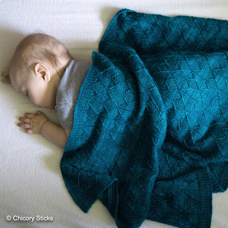 Baby laying on a bed covered in Sérac Baby Blanket from Chicory Sticks