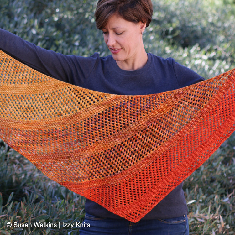 Woman holding up Izzy's California Fade Shawl designed by Ariane Gallizzi - Izzy Knits Exclusive Knit Pattern