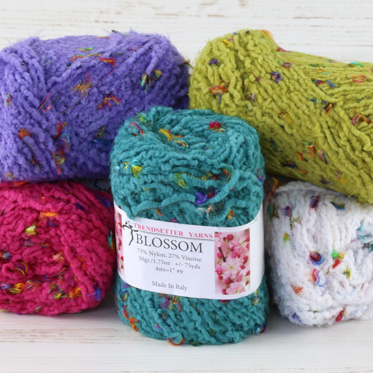 Multiple balls of Trendsetter's Worsted Blossom Yarn in various colors