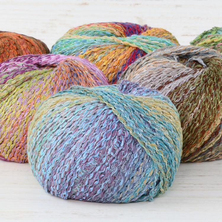 Balls of Trendsetter's Fleur Worsted Yarn in various colors