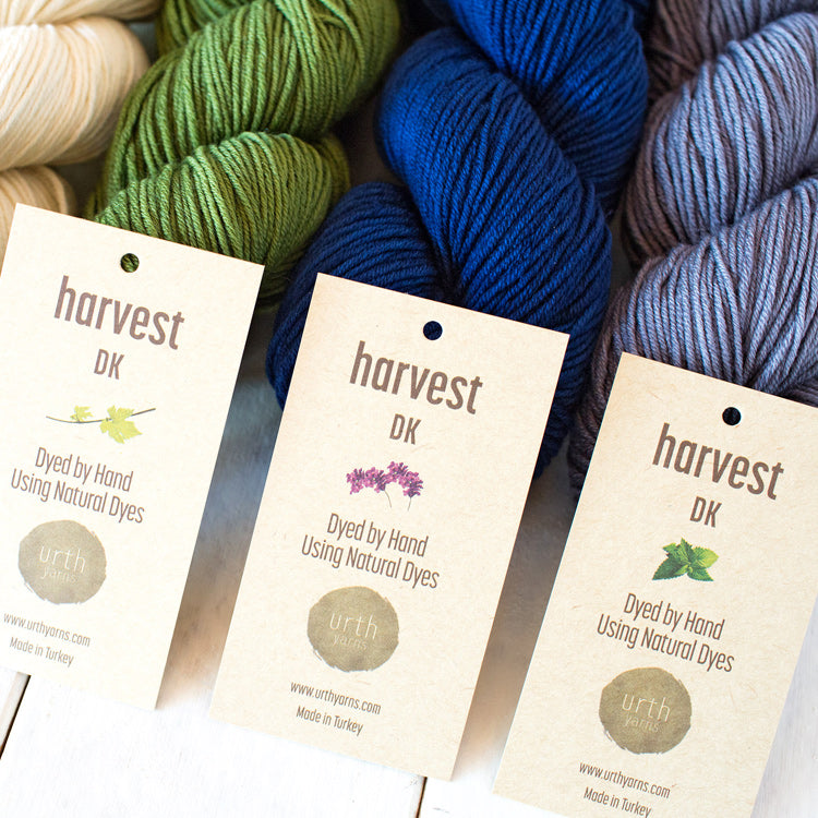Multiple skeins of Urth's Harvest DK Yarn (dyed by hand using natural dyes) on a table in various colors