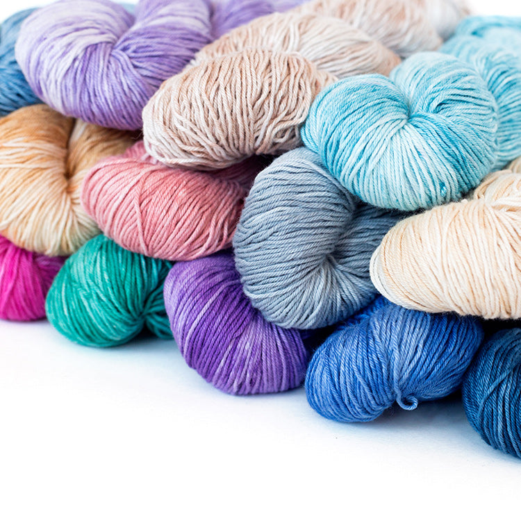 Multiple skeins of Urth Yarns' Monokrom Cotton DK 100% mercerized cotton in various colors
