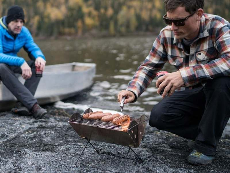 man cooking on the uco flatpack camping grill