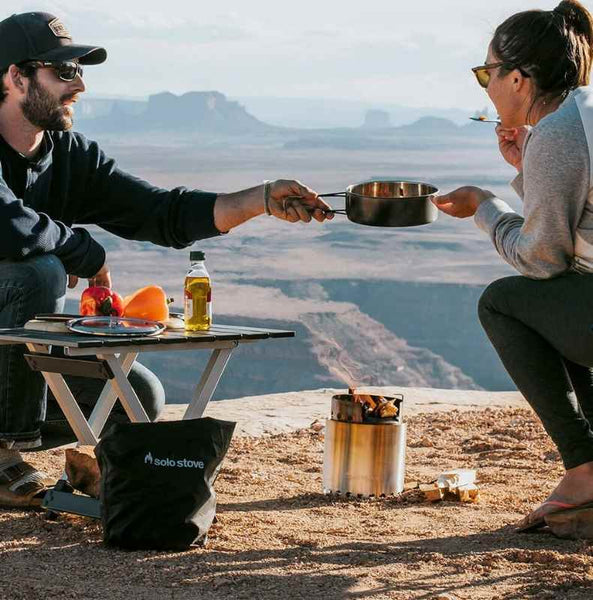 man and woman cooking solo stove campfire in desert