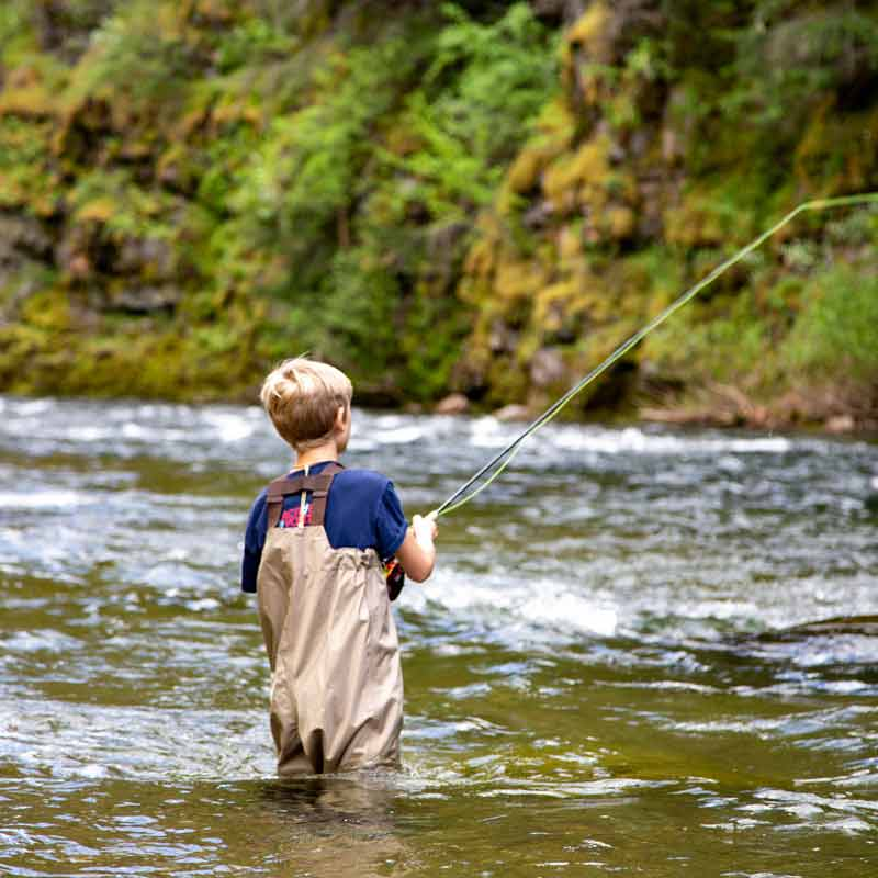 boy fly fishing on river