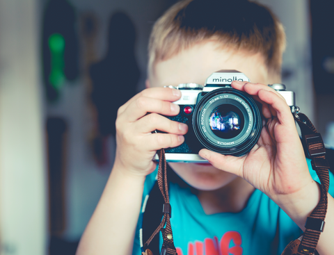 photo of boy holding film camera