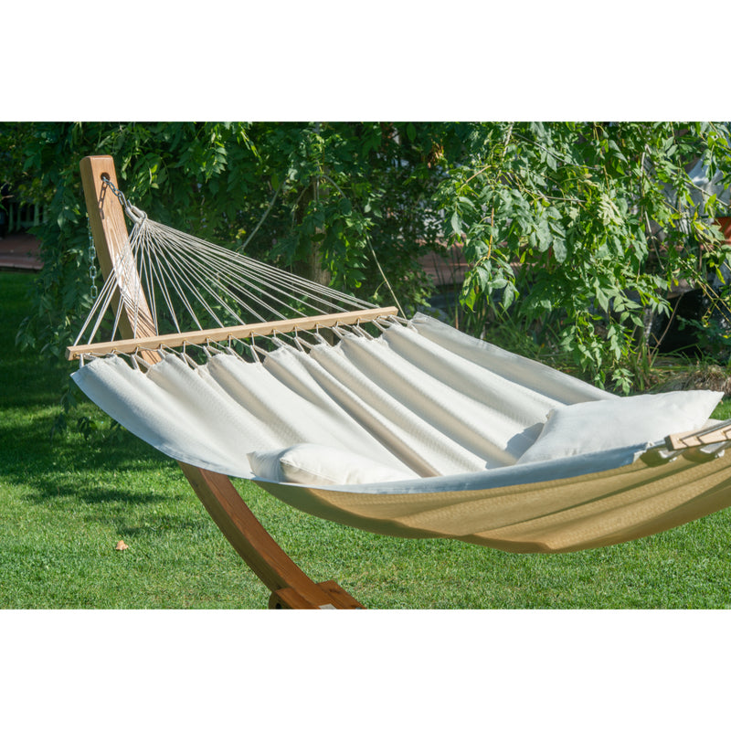 wooden hammock stand and white hammock outside in garden