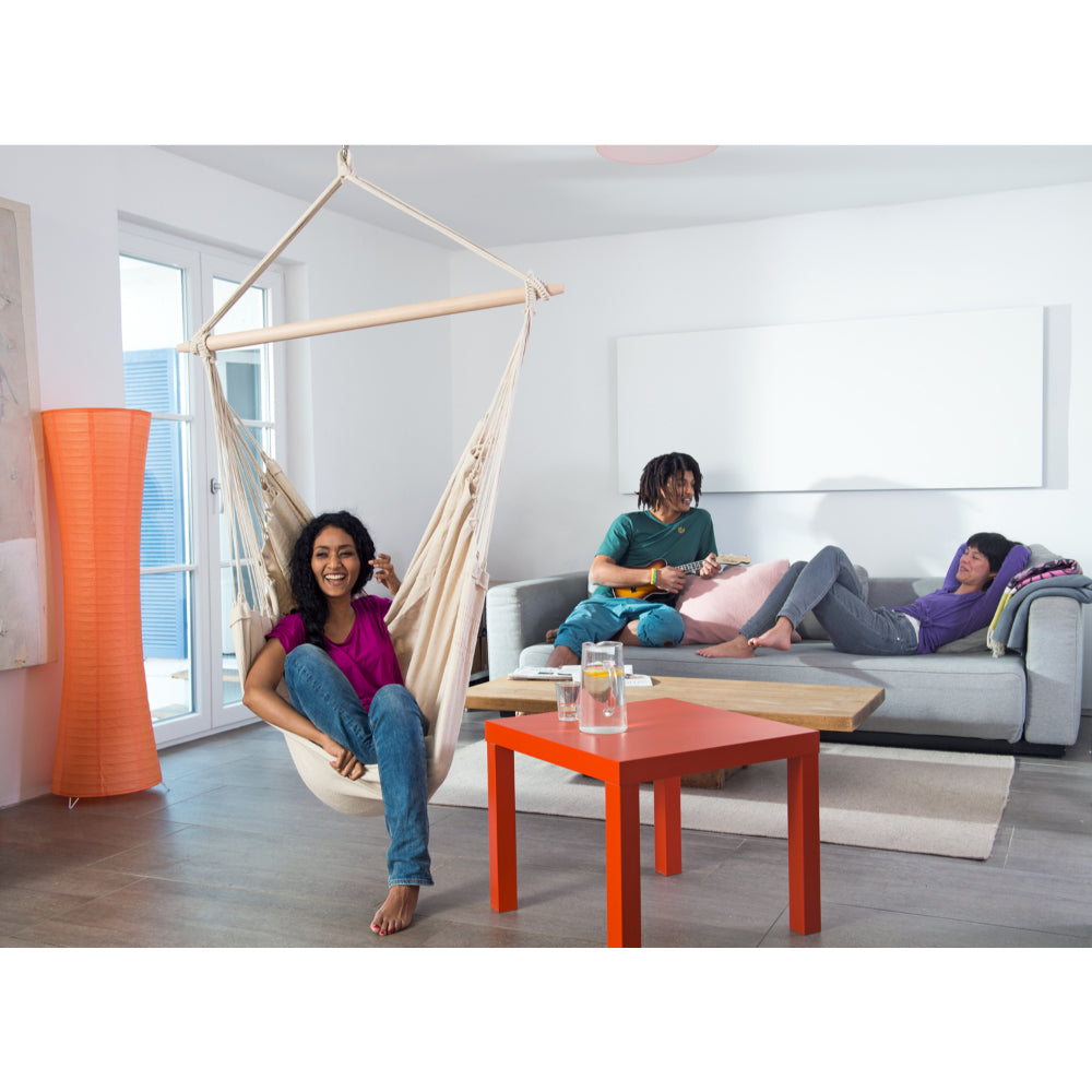 Laughing woman enjoying indoor hammock swing chair