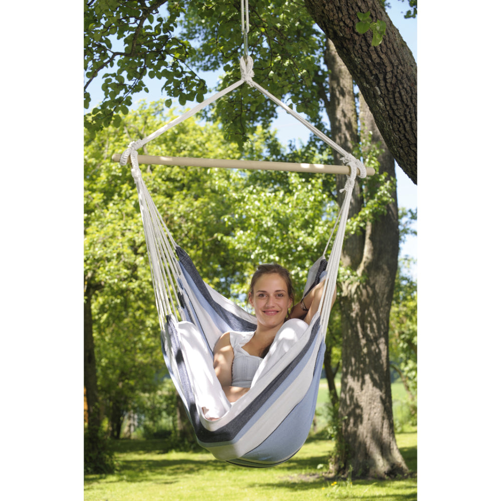 woman resting in hammock chair hung from tree branch
