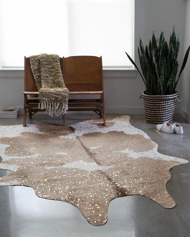 Neutral colored faux fur hide rug with metallic gold accents makes fashion statement in a living room