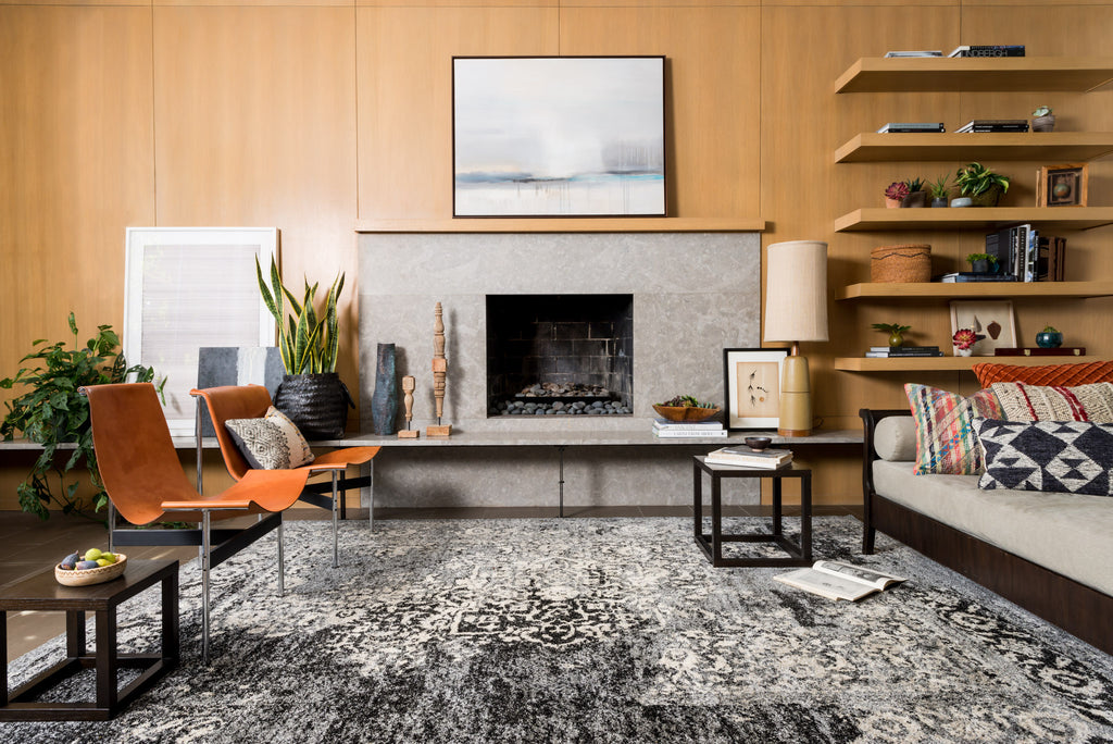 These warm pine walls with built-in shelves and the concrete fireplace bring a soft industrial feel to this family room. The black and white rug has carved details that ensure the style in this room starts from the floor up.