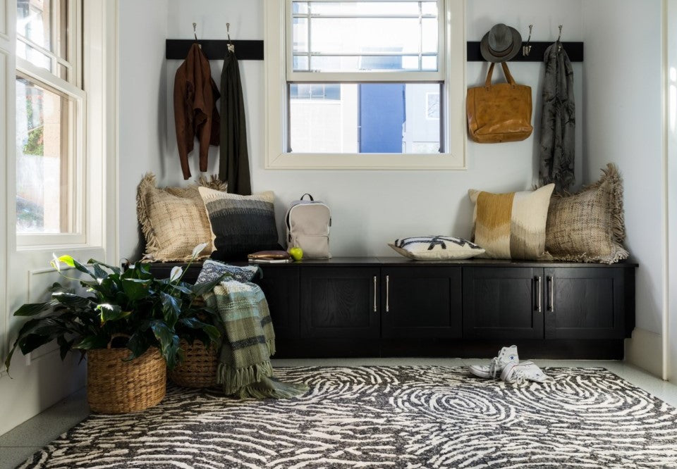 Dark cabinet seating, throw pillows, coat hooks, and a fun, textural rug combine to make this mudroom the only stop you need to make on your way out of the house.