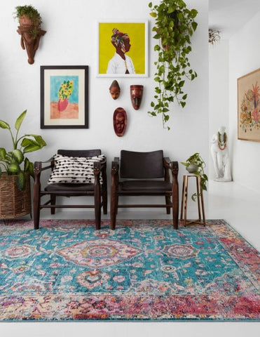 Eclectic wall art, bright colors, and lots of indoor plants contribute to the eclectic bohemian style of this entry way, and the modern take on a traditional rug ties it all together.