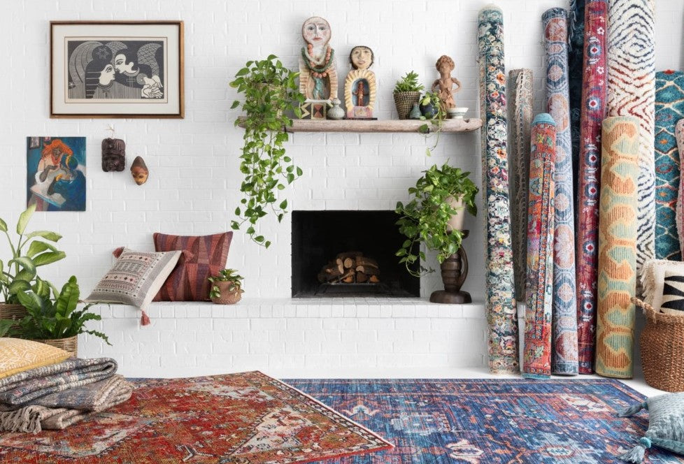 Diverse sculptures and prints bring a worldly flair to this fireplace, and with all those rugs to choose from they're sure to have an visually vibrant home.