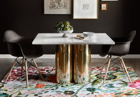 A bold floral rug offsets the dark walls and furniture, while providing a perfect stage for the marble-topped golden table to shine.
