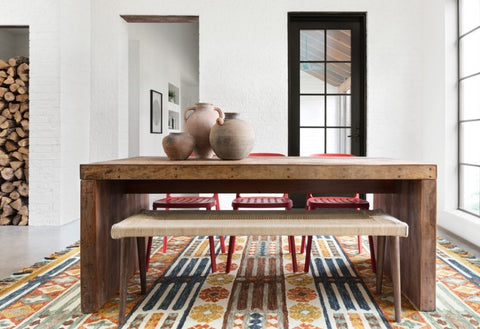 The handmade, natural wool in this rug perfectly compliments the simple wooden table in this dining room.