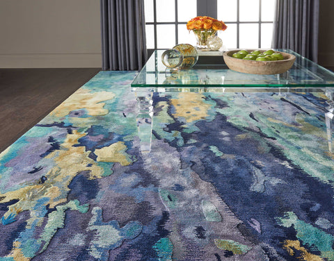 The beautiful watercolor-like pattern on this modern rug is shown off through the acrylic table in this living room.