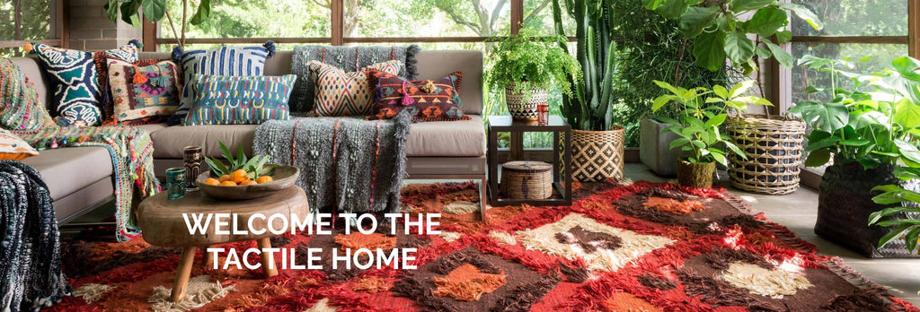 Lush and colorful living room filled with green house plants, a modern grey sofa piled high with textured decorative pillows. A red, brown and cream color shag area rug is the foundation of this tactile environment.