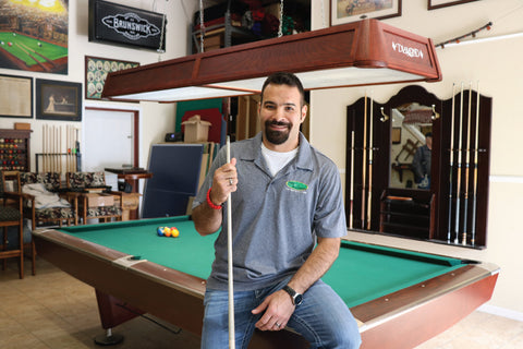 Juston Markell taking a candid shot during a game of pool at his shop in Michigan