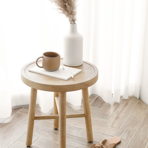 Stool with a cup, note and a vase on top. White curtains in the back.