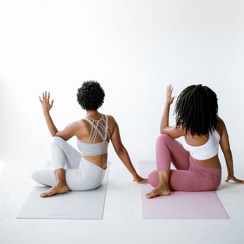 Two ladies doing a yoga pose with their backs turned to the front sitting down on mats