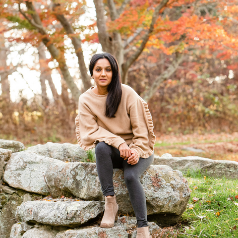 Far Momin founder of She Plants Love sitting on rocks outside on a fall day.