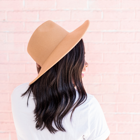 Back of a lady wearing a white t-shirt and a hat.