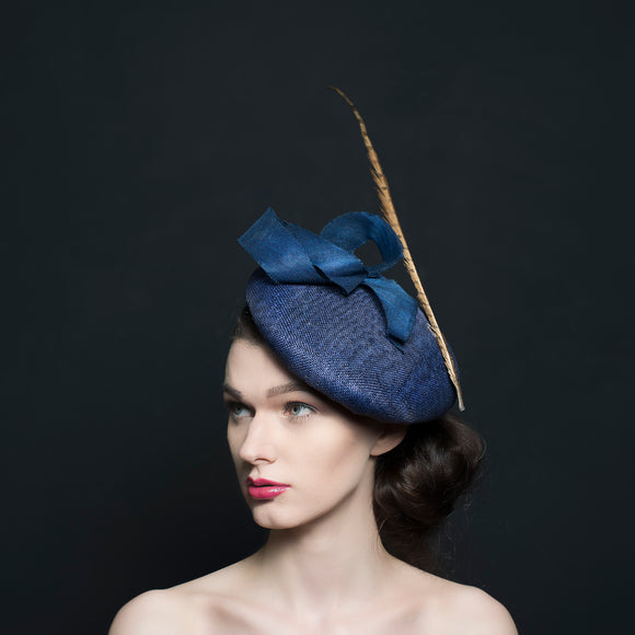Navy large button beret fascinator/hat with navy trimming and a gold pheasant feather.Rivka Jacobs mllinery