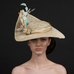 Latte coloured sinamay brimmed hat, with a spray of diamond cut feathers in light orange, coffee, cream. Hand made by Rivka Jacobs Millinery